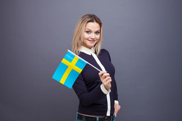Immigration and the study of foreign languages, concept. A young smiling woman with a Sweden flag in her hand.