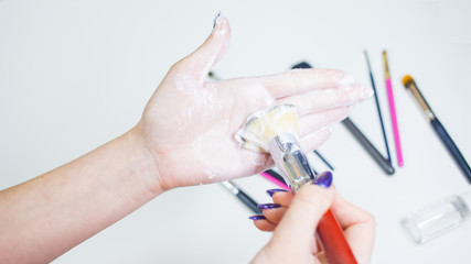 Cleaning and care of makeup brushes, women's hands wash the brush from cosmetics,
