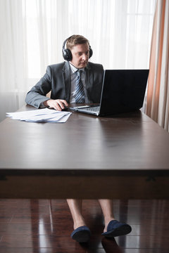 Young man in gray suit, shirt with bare feet in slippers at telework due to quarantine of coronovirus pandemic COVID-2019.Remote work at home table.Online conference on headset by laptop with boss