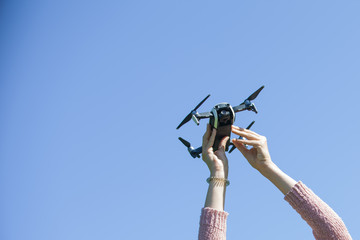 Female hands hold a drone on a background of blue sky. Catch a drone.