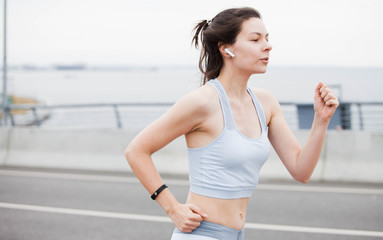 Fitness sport girl on intensive evening run, attractive runner jogging outdoors, female jogger in bright sportswear.