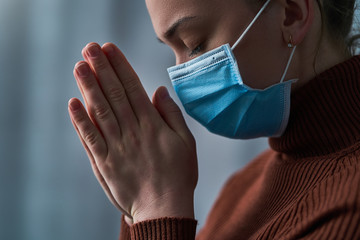 Woman in protective mask with closed eyes and praying hands, asks god for healing and recovery during disease, coronavirus outbreak and flu covid epidemic. Faith and hope during health problems Fotomurales
