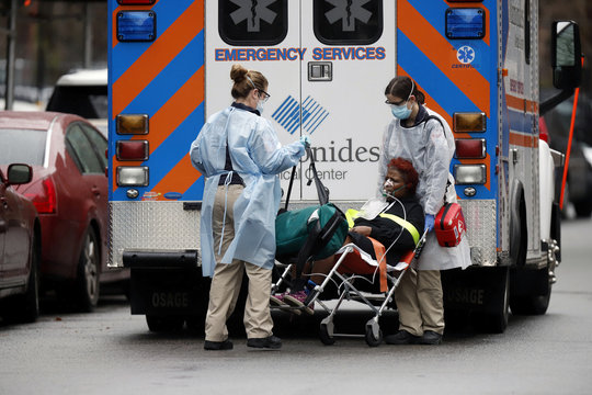Emergency Medical Technicians (EMT) wearing protective gears wheel a sick patient to a waiting ambulance during the outbreak of coronavirus disease (COVID-19) in New York City