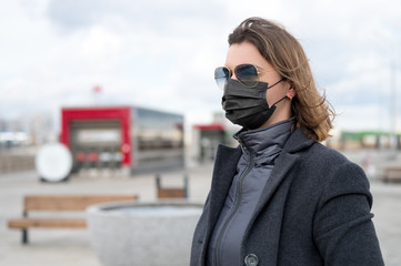 Fashionable stylish scared woman in protective black face mask, sunglasses, gray wool coat on the street near metro station. Self protection in transport during quarantine from coronavirus covid-2019