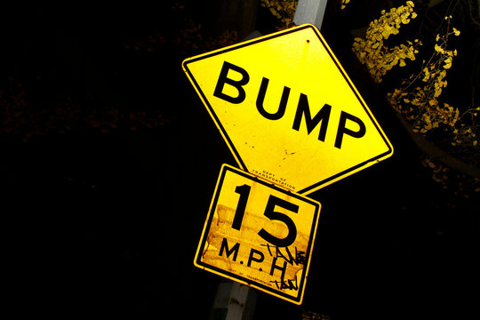 Bump Sign with 15 MPH speed limit of the Department of Transportation. Black Background with Bright Traffic Sign.