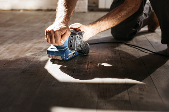 Men's hands make repairs at home. Grinding machine with a wooden floor.