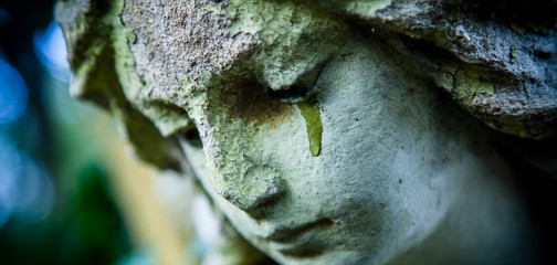 Fototapete - Death concept. Close Up of ancient stone statue of crying sad angel with tears in face as symbol of end of human life. Horizontal image.