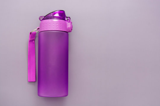 Plastic reusable water bottle over grey background, drinking water.