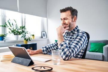 Joyful man working from home. Successful freelancer looking on digital tablet.