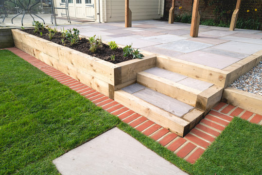 New steps in a garden or back yard leading to a raised patio, alongside a new raised flowerbed made using wooden sleepers. A mowing strip of bricks is in front of newly laid turf.