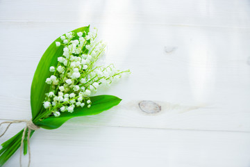 Photo sur Toile Muguet de mai bouquet of lilies of the valley on a wooden white background
