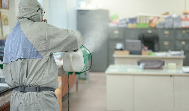 Disinfecting of office to prevent COVID-19, person in white hazmat suit with disinfect in office, coronavirus concept