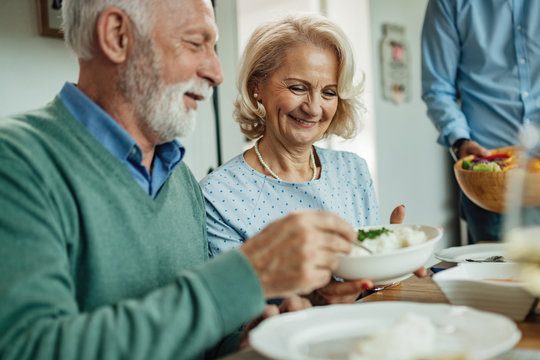 Happy senior woman and her husband enjoying in a lunch at dining table.