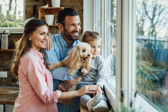 Happy family with a dog looking through the window at home.