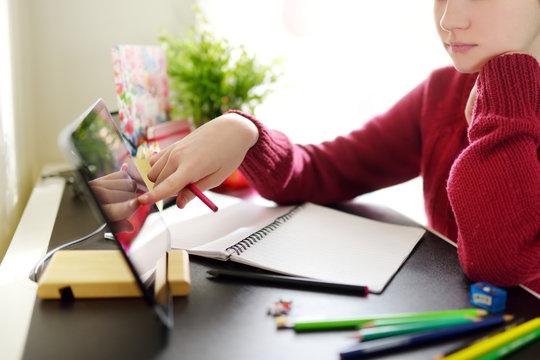Preteen schoolgirl doing her homework with digital tablet at home. Child using gadgets to study. Education and distance learning for kids. Homeschooling during quarantine.