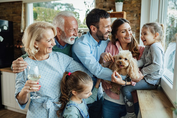 Happy extended family with a dog having fun at home.
