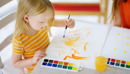 Cute girl drawing with colorful paints. Creative kid painting at home. Education and distance...