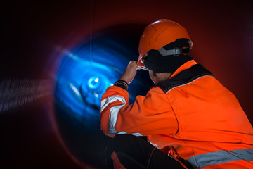 Pipeline construction worker in reflective protective uniform inspecting pipe tube for natural gas distribution. Oil industry construction.