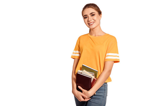Beautiful, female student in a yellow T-shirt, holds books and notebook. Get an education, prepare for classes in college, institute. Young graduate. White background, isolate. Copy space.