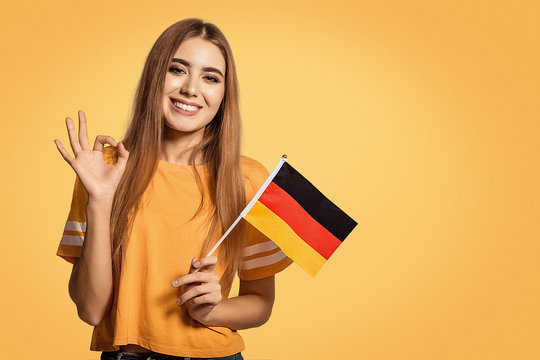 A beautiful young woman holds in her hands the flag of Germany and shows the OK sign. Exchange student, learn Germanic language. Tourist traveling. Football fan.