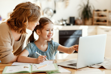 Fototapeta Happy girl with mother studying online at home. obraz