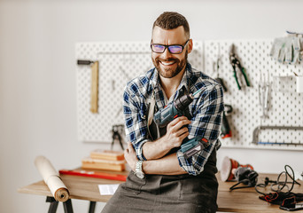 Cheerful craftsman with drill looking at camera Fotobehang
