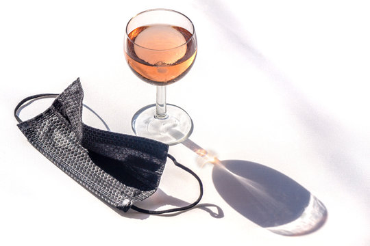 Medical face mask black next to a glass of rose wine on a white background copy-space. Concept of social activities during pandemic and crown virus quarantine.