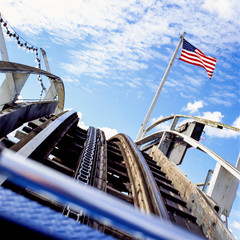 Rollercoaster with American US flag and sky. Risk, volatility, instability, up and down concepts. Motion blur effect.