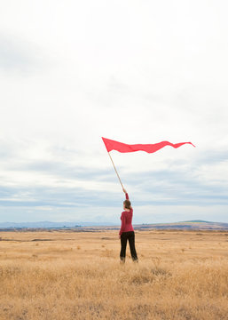 People woman alone outdoors in field waving signal flag banner. Communication, isolation, social distancing  concept.