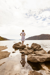 Rear view woman standing by water on shore of river or lake. People alone outdoors in beautiful nature looking at view. Peace, solitude, social distancing concept.