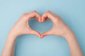 Top pov above overhead close up view photo of hands making shape of heart isolated over blue pastel color background
