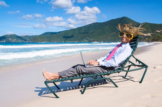 Businessman in straw hat and giant sunglasses typing on his laptop on a beach chair working remotely from the shore of an empty tropical beach