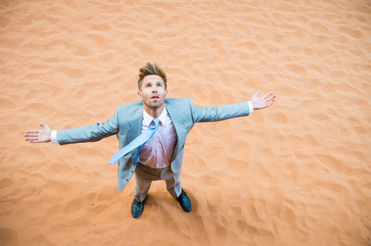 Solitary businessman standing on red sand desert looking up into the heavens with arms outstretched
