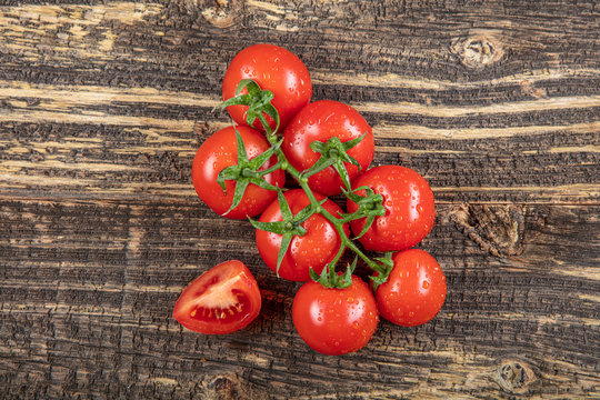 Fresh grape tomatoes with for use as cooking ingredients on wooden background.
