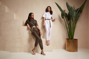 Foto op Canvas Marokko Two beautiful woman fashion model brunette hair friends wear overalls suit casual style sandals high heels accessory clothes safari Sahara journey summer hot collection plant flowerpot wall stairs.