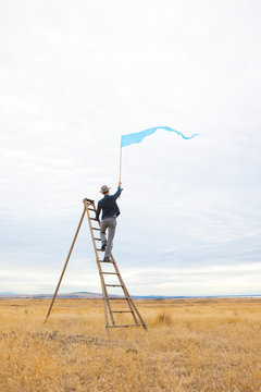 People man alone on ladder outdoors in field waving signal flag banner. Communication, isolation, social distancing  concept.