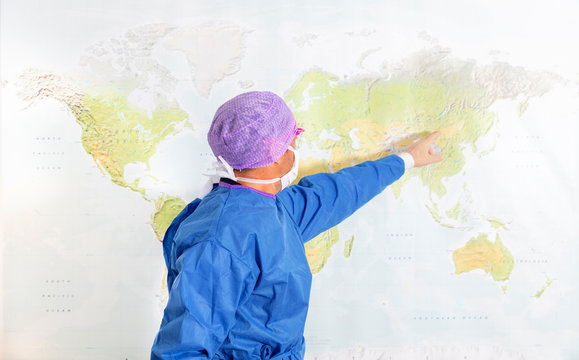 Doctor pointing at world map