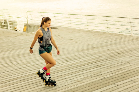 Young attractive sport woman roller skating on the beach