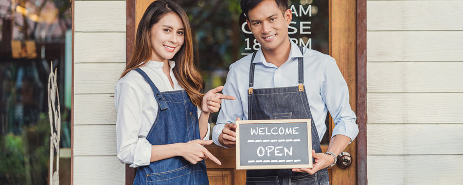 Banner of Asian partner Small business owner hands holding and showing the chalkboard with Welcome Open sign in front of coffee shop, startup with cafe store, installing open and close label concept