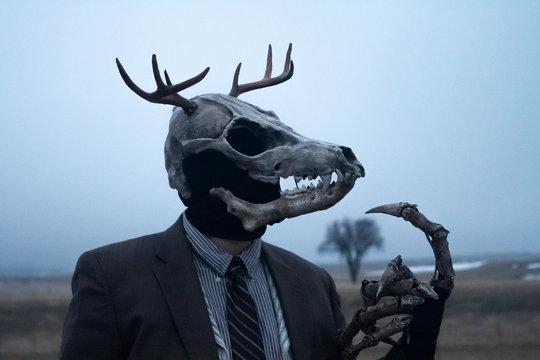 Wendigo masked man in the fog wearing suit and tie