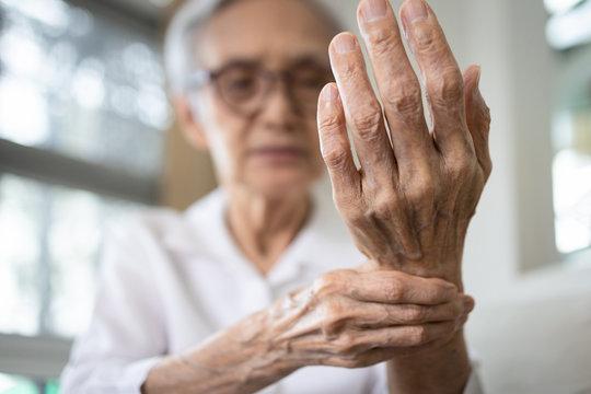 Elderly female patient suffer from numbing pain in hand,numbness fingertip,arthritis inflammation,beriberi or peripheral neuropathies,senior woman massage her hand with wrist pain,rheumatoid arthritis