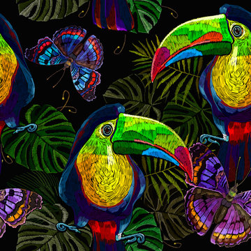 Toucan birds, palm leaves and colorful butterflies, seamless pattern. Embroidery art. Jungle paradise background. Fashionable template for design of clothes, textiles