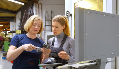 A young trainee receives tuition from her trainer. Both women work as computerized  numerical control engineers. They are seen at their high tech place of work.