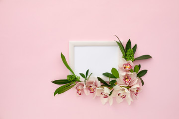 Keuken foto achterwand Orchidee photo frame decorated with green leaves and orchid flowers on pink pastel background. empty space for text. mock up with copy space. Flat lay