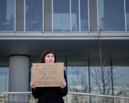 "Woman holds sign saying "" I lost my job because of coronavirus."""