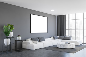 Gray living room corner with sofa and poster