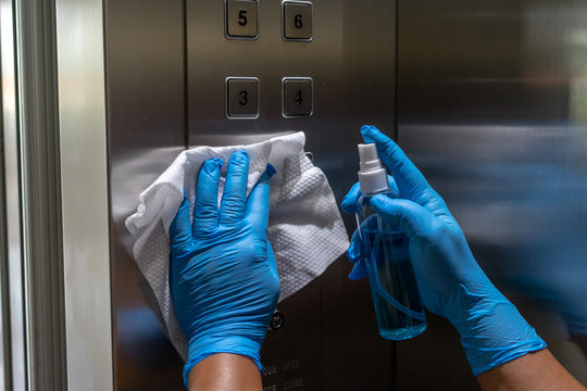 Close up of female hand using wet wipe and alcohol sanitizer spray bottle to clean an elevator push button control panel.Disinfection ,cleanliness and heathcare,Anti Corona virus (COVID-19)
