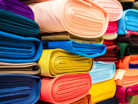 Rolls of bright multicolored fabric close-up. Coils of fabric are on the shelves in the store. Sample of coat cotton fabric in rolls