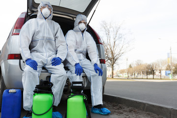 Men in biohazard suits sitting in car with disinfection chemicals