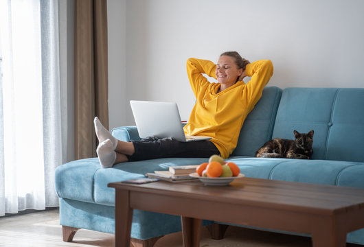 Happy young woman in a yellow sweatshirt works at home on a blue sofa with a laptop and a cat, remote work and education, staying home during a virus